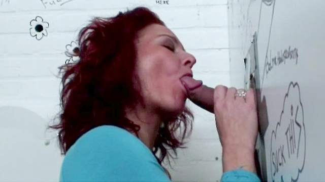 Hot brunette Petra is sucking a dick through the hole