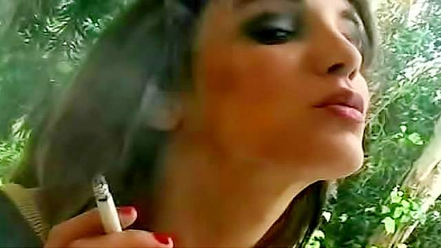 Daring and good looking brunette is smoking cigarette outdoors